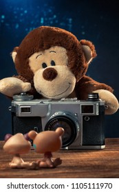 Plush monkey with an old film camera photographing toy animals