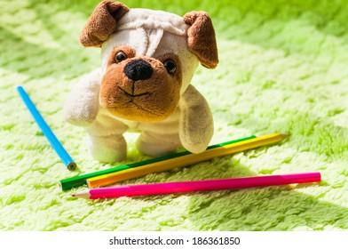 Plush puppy chooses a crayon