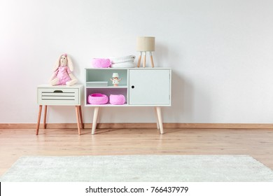 Plush rabbit on white bedside cabinet next to cupboard with lamp and pink DIY bags in child's room