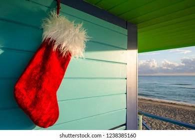 Plush red velvet Santa stocking hanging in front of the bright tropical colors of a classic lifeguard tower in front of a scenic view of Miami Beach, Florida, USA