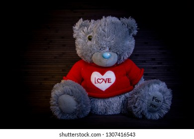 Plush, soft toy Bear. Red knitted t-shirt with white heart. Love, romantic evening.