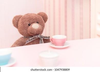 A plush teddy bear at a tea party