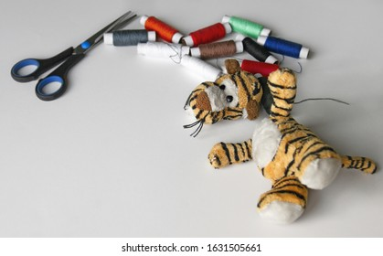 Plush tigger with a torn head. Sewing kit. Torn toy.