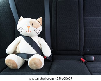 Plush toy cat fastened with seatbelt in the back seat of a car, safety on the road. Protection concept.