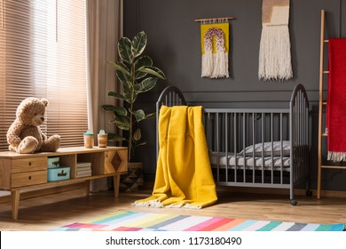 Plush toy on wooden cupboard next to grey bed with yellow blanket in child's room interior. Real photo