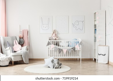 Plush toy and pillow on white round carpet in baby's room with grey armchair and posters on wall