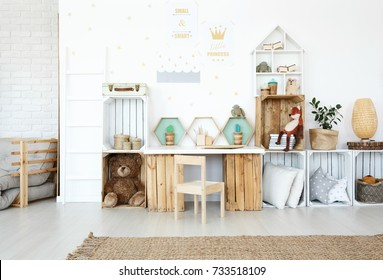 Plush toys and pillows on wooden handmade shelves in child's room with posters on wall