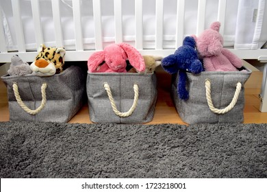 Plush toys stored in baskets under toddler crib in tidy baby bedroom