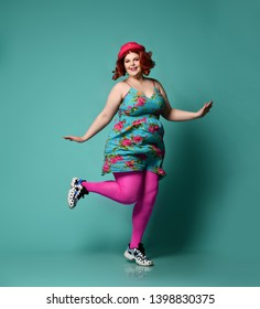 Plus-size fat chubby woman in hat and colorful clothes sundress dances twist or runs funny on popular mint background
