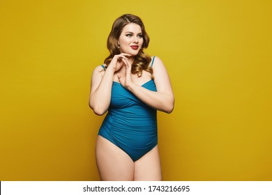 Plus-size model girl in swimsuit isolated at the yellow background. Fat woman in swimsuit on yellow background. Pin-up style photo. Copy space to advertise
