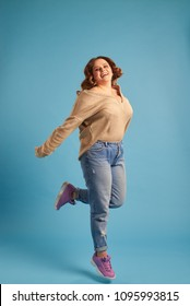 Plus-size woman jumping in excitement at studio