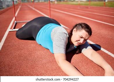 Plus-sized female fallen down racetrack during hurdle marathon