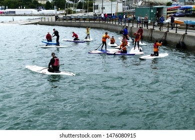 Plymouth England 2019. Mount Batten Watersport center. Several people learning to paddle board under the supervision of an instructor. All dressed in the appropriate gear with helmets.