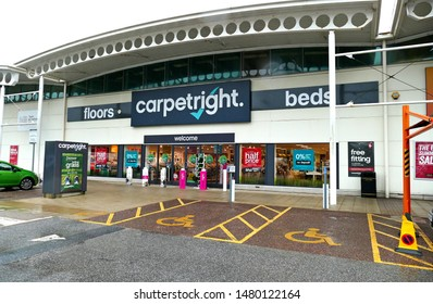 Plymouth England August 2019. Carpetright. Full Facade of retail store. Sells carpets and other flooring. National chain. dark blue sign white writing. Parking bays.