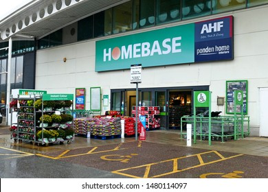 Plymouth England August 2019. Homebase superstore full facade with racks of flowers and stacks of compost for sale outside. Parking bays