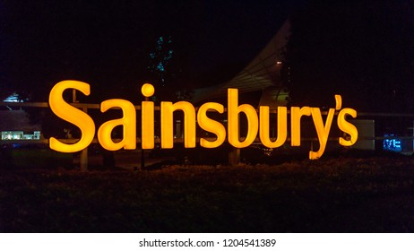 Plymouth, England - Oct 10, 2018: Sainsburys Shop Sign by Night, shallow depth of field horizontal photography