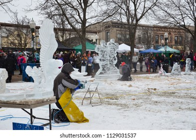 PLYMOUTH, MI / USA - JANUARY 13, 2018:  An ice carver works on an eagle piece at the Plymouth Ice Festival