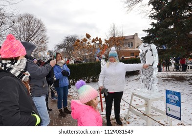 PLYMOUTH, MI / USA - JANUARY 13, 2018:  A woman points to the Michigan map on a carving at the  Plymouth Ice Festival
