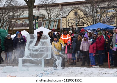 PLYMOUTH, MI / USA - JANUARY 13, 2018:  An ice carver works on a mermaid piece at the Plymouth Ice Festival.