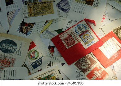 Plymouth, MI/USA: July 3, 2017 - Sunlight on randomly scattered loose USA definitive stamps. Philatelists enjoy these common stamps with various designs showing local culture or historical interest.