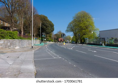 Plymouth, UK.  13/4/20: An empty road with clear air and green trees in the background on a bright sunny day.