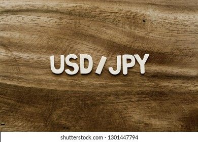 "Plywood alphabets on acacia wooden texture background concept. The word ""USD/JPY (United States Dollar to Japanese Yen)"" on wood pattern backdrop."