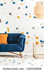 Plywood lampshade above a side table with golden frame and a dark blue sofa in a white living room with lastrico pattern. Real photo.