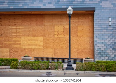 Plywood shutters prevent unauthorized access by squatters, looters or vandals to unused, vacant, or abandoned property. Economic recession concept bankrupt business boarded up with plywood sheets.