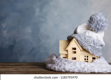 Plywood toy house with warm hat, scarf and space for text against color background. Heating system