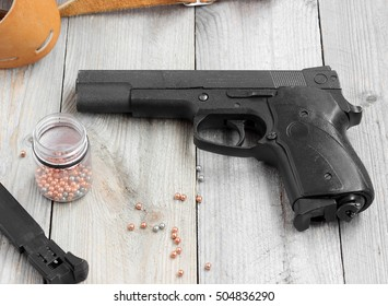 Pneumatic (gas) gun, magazine, holster and balls for shooting at a wooden table.