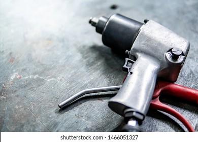 Pneumatic wrench on concrete floor in auto repair shop. Car wheel repairing concept
