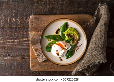 Poached egg with avocado cream and spinach on the old wooden table horizontal