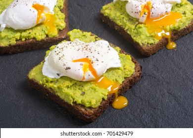 Poached egg and avocado mexican sauce guacamole on toast .