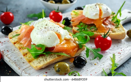 Poached egg on grilled toast with smoked salmon, rucola, olives and vegetables on white board. healthy breakfast