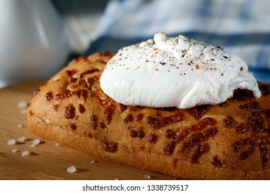 Poached egg on a slice of bread on a wooden surface