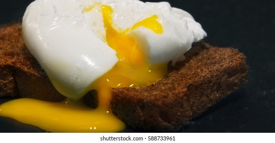 Poached egg on a slice of wholemeal bread. Photo on a black background