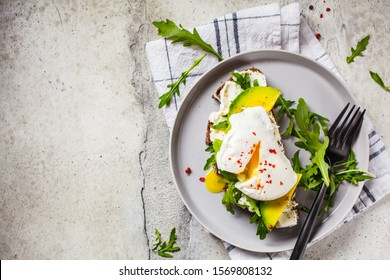 Poached egg toast with avocado, cream cheese and rye bread on a gray plate, top view. Healthy food concept.