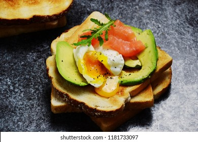 Poached egg toast isolated. Breakfast tost with poached egg, avocado and salmon on the black background