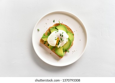 Poached eggs on toasted bread with avocado, rukola and herbs over white stone background with copy space. Top view, flat lay