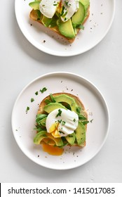 Poached eggs on toasted bread with avocado, rukola and herbs on light background. Top view, flat lay