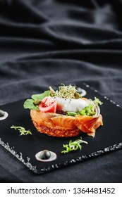 Poached eggs with salad, baked salmon, tomatoes, red radish, olives, and peppermint leaves on a black slate plate and dark table cloth as a gourmet restaurant dish. Hands cutting egg with a knife