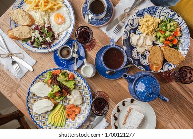 Poached eggs with salmon and avocado on sourdough toast isolated on wooden background. Homemade food. Top view. eating and leisure concept - group of people having dinner at table with food
