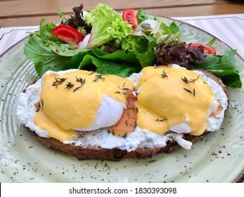 Oeufs pochés avec sauce à sauce de saumon, sauce hollandaise, yaourt mayonnaise sur crostini au pain rôti de pain et salade pour le petit-déjeuner.