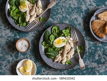 Poached mackerel, spinach and egg salad on a dark background, top view. Delicious healthy food concept