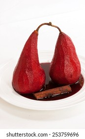 Poached pears in red wine isolated on white