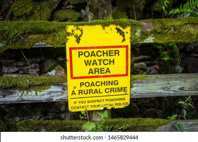 Poacher Watch Area. Warning sign attached to a wooden fence and covered in moss. Warning of rural crime. Instruction to inform local police