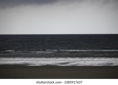 POA,SAO PAULO,BRAZIL - The dark sand, the reflection of the sky, the gray sea and the misty sky in horizontal tracks.