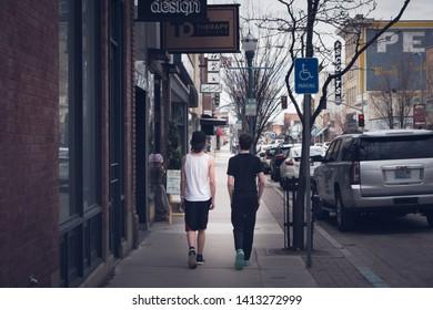 Pocatello, ID/USA- 4/13/19: Two teenage boys walk along the sidewalk among the city shops in Old Town Pocatello, Idaho.
