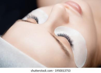 Pocedure Eyelash extension. Woman master combs lashes 2d.