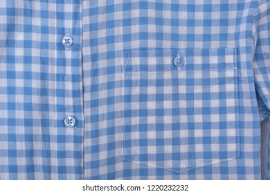 Pocket and buttons on a blue checkered shirt. Close-up.